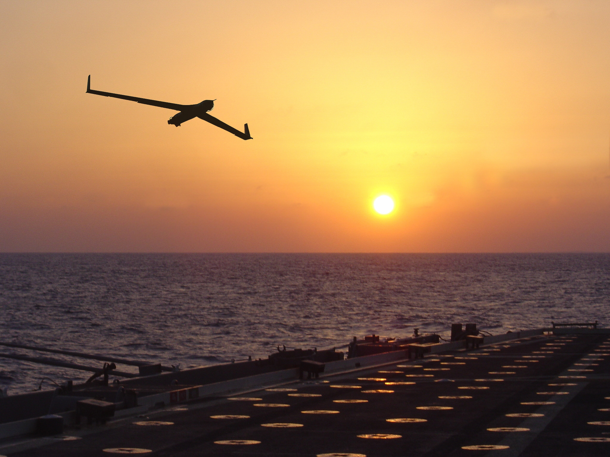 ScanEagle flying over a ship at sea.